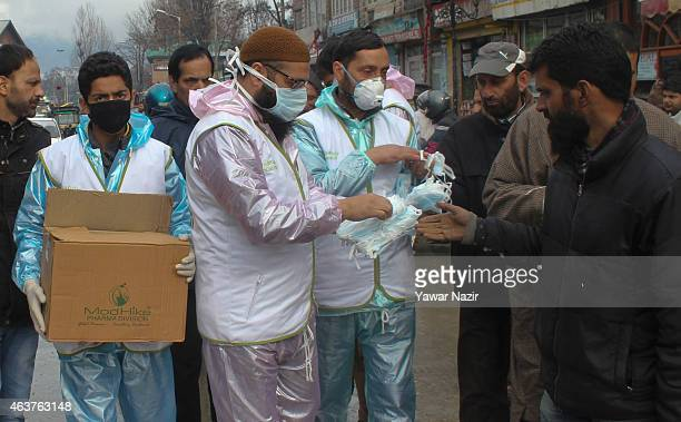 Kashmiri Muslim members of a nongovernmental organization distribute masks to people in the city center after two patients infected with H1N1 virus...