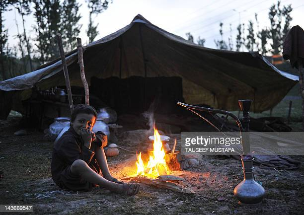 Kashmiri Muslim nomad boy sits outside a tent in Srinagar on May 2, 2012. Nomads travel with their livestock and trek through the state's rugged...