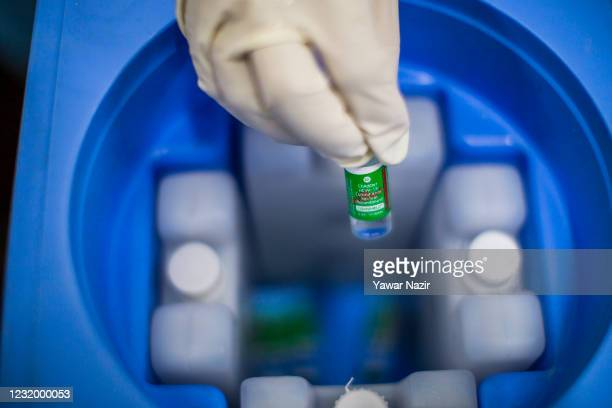Kashmiri Muslim Nurse holds up a vial of the Covishield COVID-19 Vaccine, the Indian-made version of the Oxford/AstraZeneca vaccine at a hospital on...