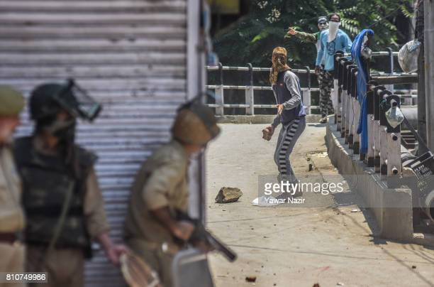 Kashmiri Muslim protester aims his stone at Indian government forces during a protest after they defied curfew on the the first death anniversary of...