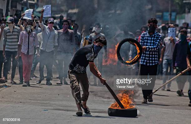 Kashmiri Muslim protester drags a burning tire during an anti Indian protest following violence that has left over 46 people dead and thousands...