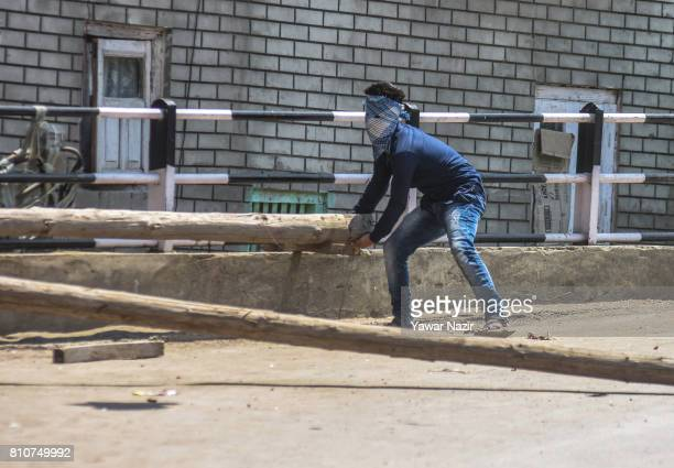 Kashmiri Muslim protester tries to block a road with a log during a protest after they defied curfew on the the first death anniversary of Burhan...