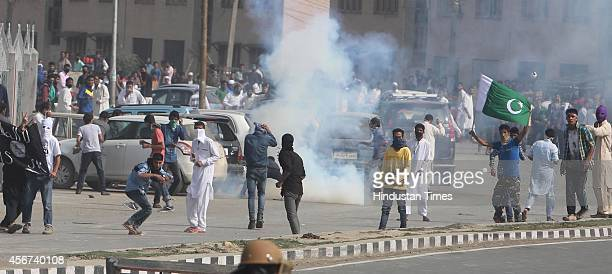 Kashmiri Muslim protesters hurl stones at the paramilitary soldiers during protests after EidulAdha prayers on October 6 2014 in Srinagar India...