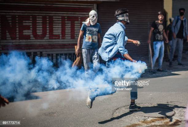 Kashmiri Muslim protesters runs with an erupting teargas shell to return it back towards Indian government forces during an antiIndia protest on June...