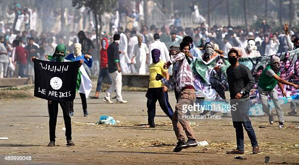 Kashmiri Muslim protesters throw stone as they carry a ISIS flag and portraits of local militants as tear gas shells exploded near them during the...
