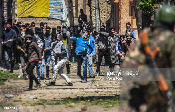 Kashmiri Muslim protesters throw stones at Indian government forces during an anti election protest over the elections of the lower house of Indian...