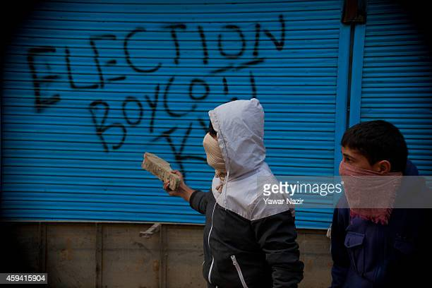 Kashmiri Muslim protesters throw stones towards Indian government forces during an antielection protest on November 22 in Srinagar the summer capital...