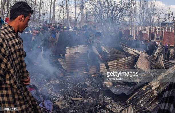 Kashmiri Muslim salvage the belongings from the debris of war ravaged residential house after a gun battle between Indian government forces and...