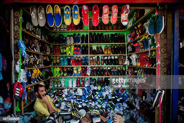 Kashmiri Muslim shopkeeper displays shoes on reduction sale as he waits for customers on September 09 2015 in Srinagar the summer capital of Indian...