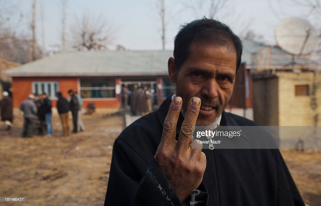 A Kashmiri Muslim village head shows his indelible ink marked finger after casting his vote outside a polling station during state's legislative council election on December 03, 2012 in Budgam, west of Srinagar, Indian Administered Kashmir. Village heads in Indian-administered Kashmir voted for their representatives in the state's legislative council after 38 years today. These grass root workers are represented by four people in the council- the lower house of Kashmir assembly. This year the village heads were attacked by unidentified gunmen in the conflict torn region. Many resigned from their post after at least 10 village heads were killed in attacks. Today's polling saw long queues despite the resistance leadership calling for a boycott. But the biggest militant group in the region- the Hizbul Mujahideen- had refrained from calling a boycott saying the polling was necessary for daily administration of the state.