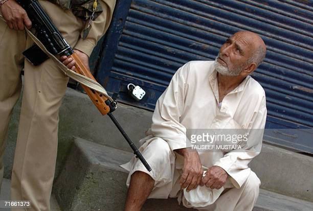 Kashmiri Muslim watches as an Indian Central Reserve Police Force soldier stands alert during a cordon and search operation at Kukar Bazar in...