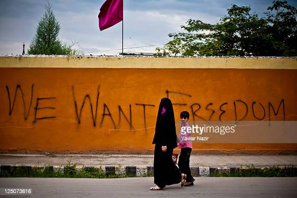Kashmiri Muslim woman and a child walk in front of graffiti written by Kashmiris on wall on September 15 2011 in Srinagar the summer capital of...