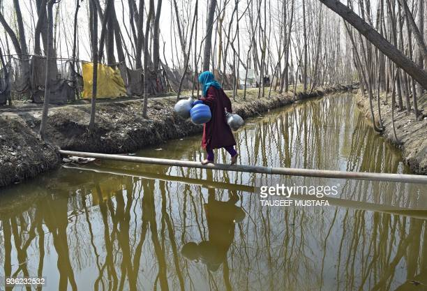 Kashmiri Muslim woman balances on a water pipe before collecting water at Dasilpora village on March 22 2018 World Water Day is held annually on 22...
