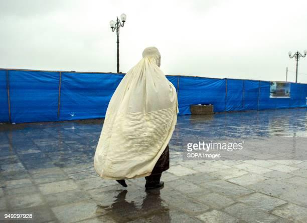 Kashmiri Muslim woman devotee walks inside the compound of Hazratbal Shrine Despite incessant rainfall thousands of devotees from across the Kashmir...