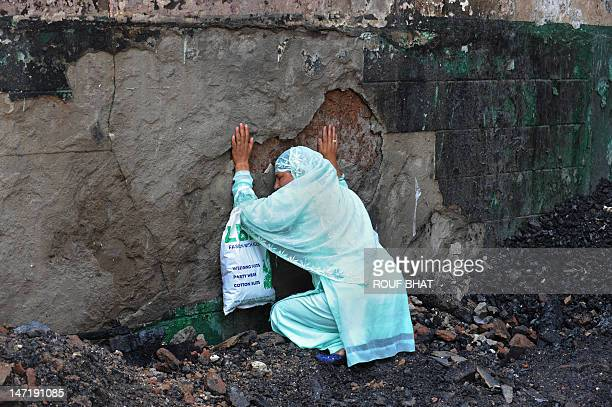 A Kashmiri Muslim woman grieves as unseen fire services personnel and volunteers clear debris from the charred remains of the 200year old shrine of...