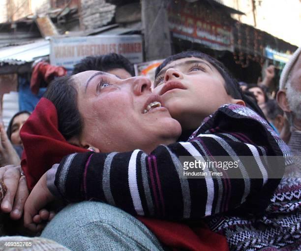 Kashmiri Muslim woman holding a child who is looking towards the holy relic of Sufi Saint Syed Abdul Qadir Jilani outside his shrine on February 14...
