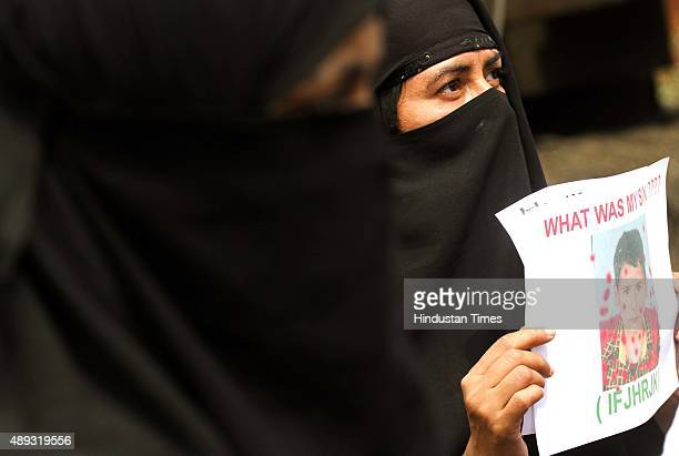Kashmiri Muslim woman holds a portrait of threeyearold Burhan Bashir during a sitin protest organised by Human Rights Group on September 20 2015 in...