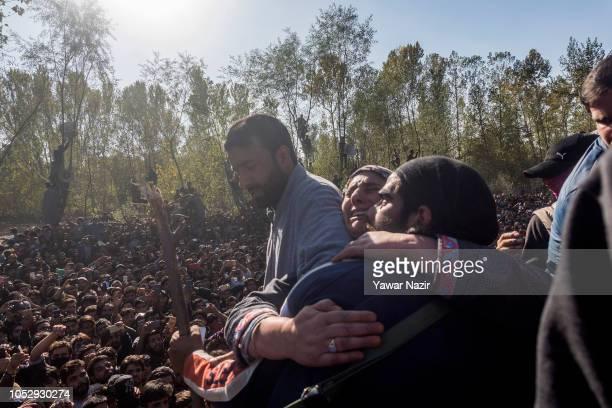 Kashmiri Muslim woman hugs a Kashmiri rebel as he attends the funeral of his comrade Sabzar Sofi a research scholar turned rebel killed in a gun...