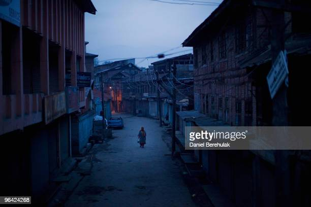 Kashmiri muslim woman negotiates curfew imposed streets on February 04 2010 in Srinagar Kashmir India Soldiers dressed in riot gear patrolled the...