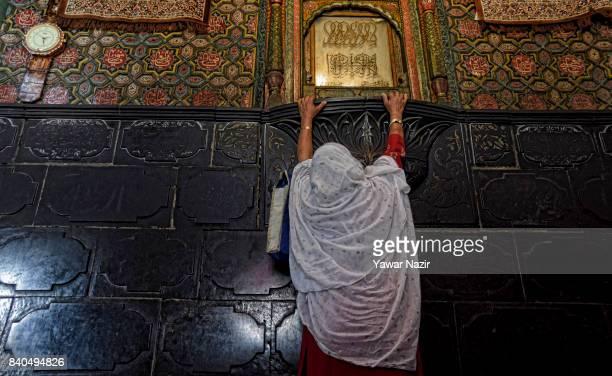 Kashmiri Muslim woman prays as she touches the wall of the shrine of Khaniqahi mullah during a festival on August 29 2017 in Srinagar the summer...