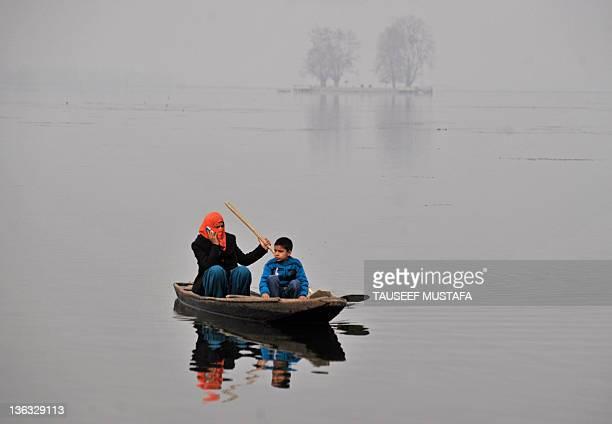 Kashmiri muslim woman speaks on a mobile phone as she sails a shikara on a Srinagar's Dal lake on January 2, 2011. North India ushered in the new...