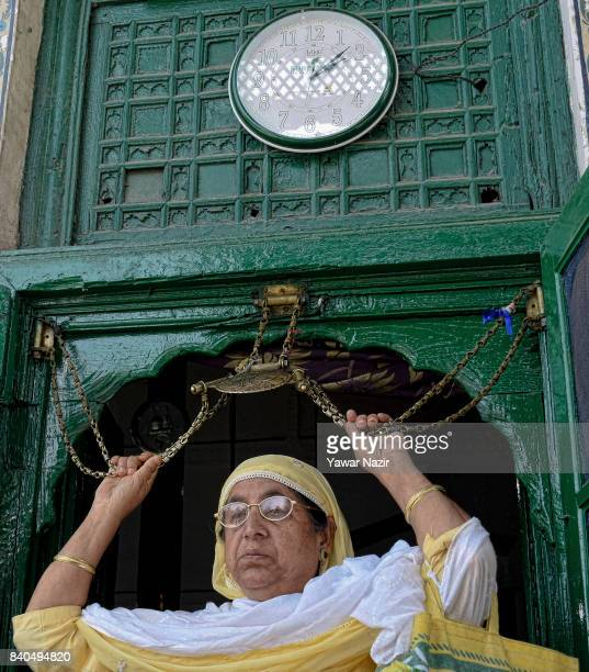 Kashmiri Muslim woman touches the chains engraved with Quran at the entrance of the shrine of Khaniqahi mullah during a festival on August 29 2017 in...