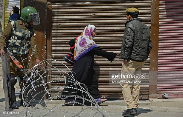 A Kashmiri Muslim woman tries to pass a barbed fence wire in the Maisuma locality of central Srinagar as police and paramilitary reinforcements...