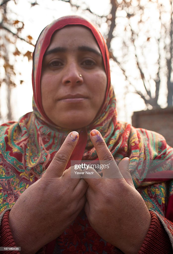 A Kashmiri Muslim woman village head shows her indelible ink marked finger after casting her vote outside a polling station during state's legislative council election on December 03, 2012 in Budgam, west of Srinagar, Indian Administered Kashmir. Village heads in Indian-administered Kashmir voted for their representatives in the state's legislative council after 38 years today. These grass root workers are represented by four people in the council- the lower house of Kashmir assembly. This year the village heads were attacked by unidentified gunmen in the conflict torn region. Many resigned from their post after at least 10 village heads were killed in attacks. Today's polling saw long queues despite the resistance leadership calling for a boycott. But the biggest militant group in the region- the Hizbul Mujahideen- had refrained from calling a boycott saying the polling was necessary for daily administration of the state.
