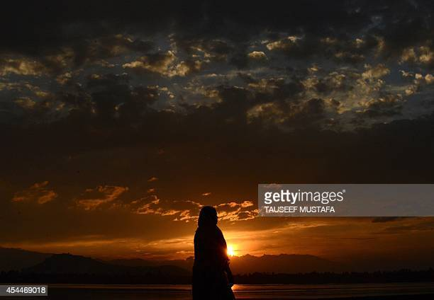 A Kashmiri Muslim woman walks on the shores of Dal Lake at sunset in Srinagar on September 1 2014 Kashmir is divided between nucleararmed rivals...