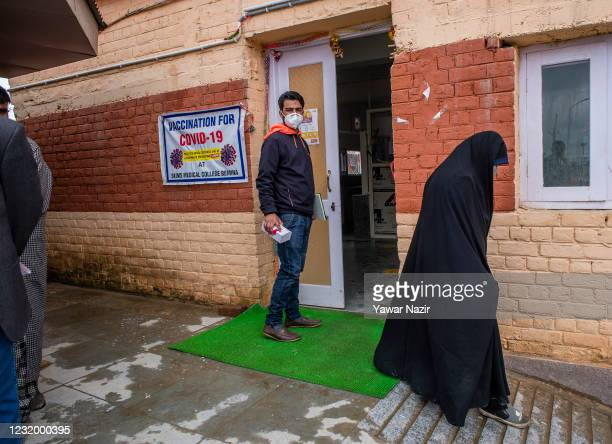 Kashmiri Muslim woman walks out of a vaccination center after taking a jab of the Covishield COVID-19 Vaccine, the Indian-made version of the...