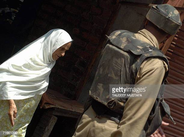 Kashmiri Muslim woman walks past an Indian Central Reserve Police Force soldier during a cordon and search operation at Kukar Bazar in Srinagar, 17...