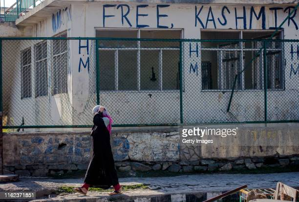 Kashmiri Muslim woman walks past graffiti saying 'free Kashmir' written on a building in the Habba Kadal on August 18 2019 in Srinagar the summer...