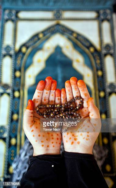 Kashmiri Muslim woman with her hands decorated with henna prays on the first day of holy month of Ramadan on July 11 2013 in Srinagar the summer...