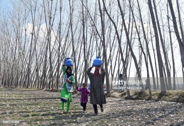 TOPSHOT Kashmiri Muslim women carry containers with water after filling them in a stream at Dasilpora village on March 22 2018 World Water Day is...