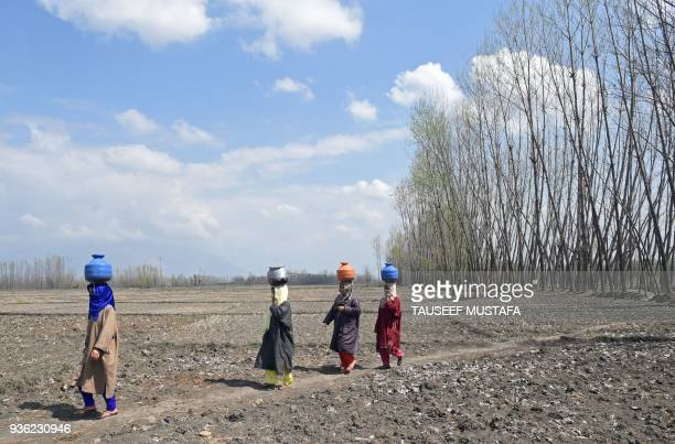 Kashmiri Muslim women carry containers with water after filling them in a stream at Dasilpora village on March 22 2018 World Water Day is held...