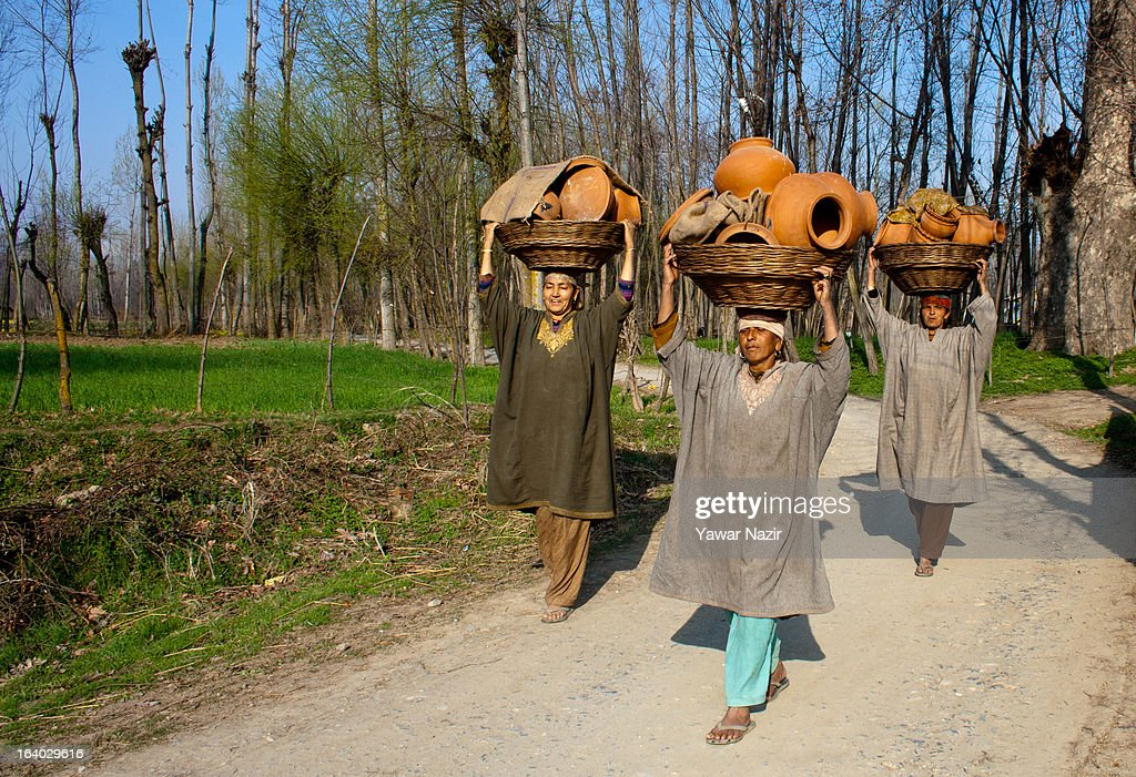 Kashmiri Muslim women carry earthen pots on their heads on March 19, 2012 in Budgam, west of Srinagar, the summer capital of Indian administered Kashmir, India. Kashmir has been a contested land between nuclear neighbors India and Pakistan since 1947, the year both the countries attained freedom from the British. Since 1947 the ownership of Kashmir has been disputed between Pakistan, India and China.