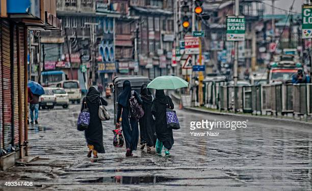 Kashmiri Muslim women, commuters walk with luggage in the deserted city center during a strike against the killing of a Truck conductor by Hindu mob...