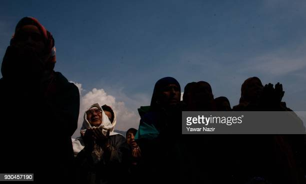 Kashmiri Muslim women devotees look towards a cleric displaying the holy relic believed to be the whisker from the beard of the Prophet Mohammed at...