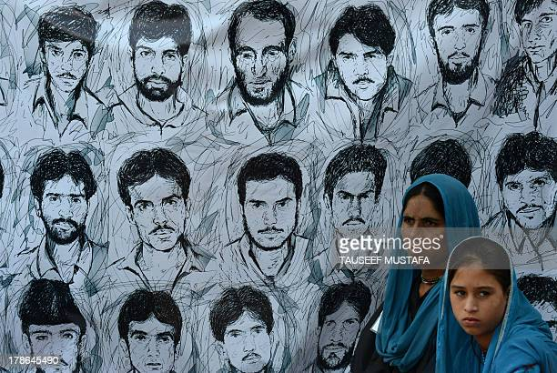 Kashmiri Muslim women from the Association of Parents of Dissapeared people are pictured in front of a banner showing portraits of missing Kashmiris...