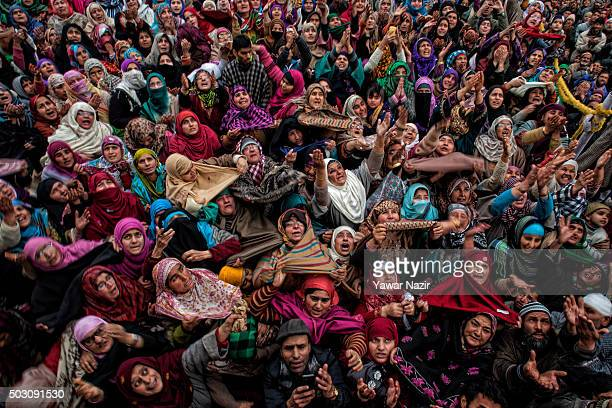 Kashmiri Muslim women look towards a cleric displaying the holy relic believed to be the hair from the beard of the Prophet Mohammed at Hazratbal...