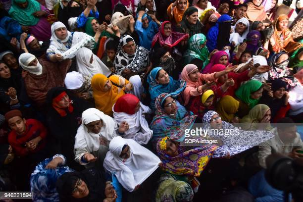 Kashmiri Muslim women pray upon seeing a relic believed to be hair from the beard of Prophet Muhammad on the occasion of the Islamic festival...
