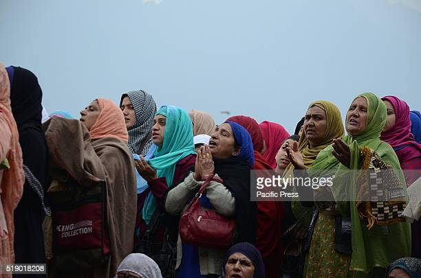Kashmiri Muslim women raise their hand in prayers as the head priest displays the relic believed to be the hair from the beard of the Prophet...