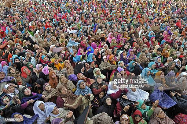 Kashmiri Muslim women react as an unseen priest shows a relic believed to be a hair from the beard of the Prophet Mohammed at the Hazratbal Shrine in...
