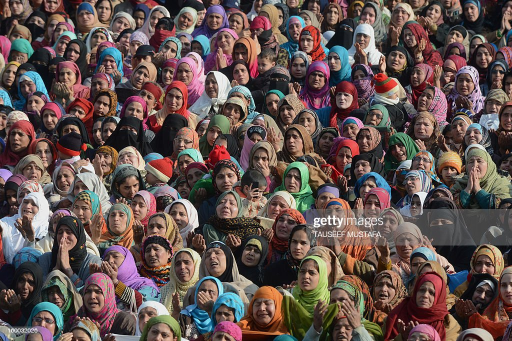 Kashmiri Muslim women react as an unseen priest shows a relic believed to be a hair from the beard of Prophet Mohammed during Eid-e-Milad-un-Nabi, the birthday of the prophet, at the Hazratbal Shrine in Srinagar on January 25, 2013. Thousands of Kashmiri Muslims gathered at the shrine in the summer capital of Jammu and Kashmir to offer prayers on the Prophet's birth anniversary. AFP PHOTO/Tauseef MUSTAFA