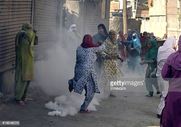 Kashmiri Muslim women run as a tear smoke canister fired by Indian Police explodes near them during a protest after Friday prayers in Srinagar on...