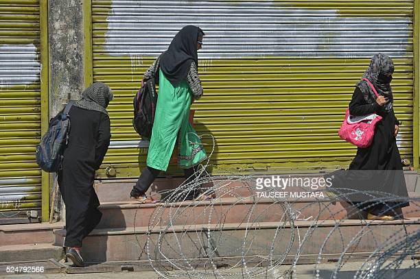 Kashmiri Muslim women try to cross a barbed fence wire in the Maisuma locality of central Srinagar as police and paramilitary reinforcements enforced...