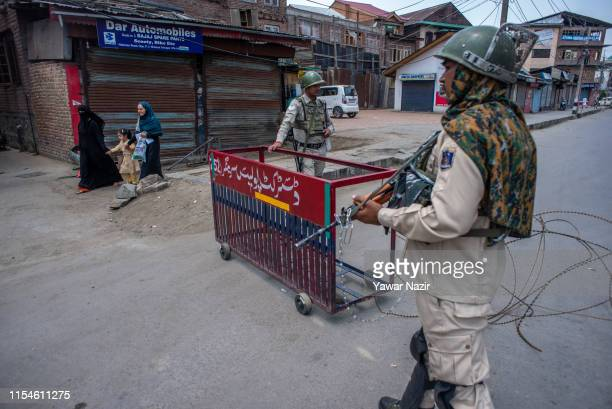 Kashmiri Muslim women walk on a deserted road as Indian paramilitary troopers stand guard during a shutdown on the third anniversary of the death of...