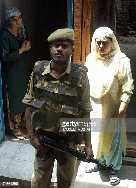 Kashmiri Muslim women watch as an Indian Central Reserve Police Force soldier stands alert during a cordon and search operation at Kukar Bazar in...