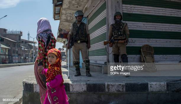 Kashmiri Muslim young girls walks as Indian paramilitary troops stands alert during restrictions in Downtown area of Srinagar city summer capital of...