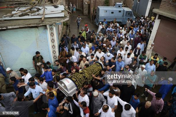 Kashmiri Muslims carry the coffin of slain editorinchief of the Srinagarbased newspaper Rising Kashmir Shujaat Bukhari during a funeral procession at...